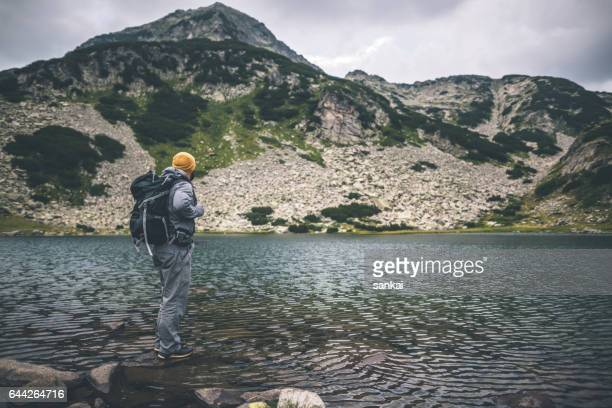traveler with a backpack stands on a stone at the lake in mountains. mountain peak in front of him. - pirin national park stock pictures, royalty-free photos & images