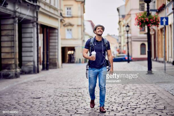 traveler with backpack and coffee admiring the architecture - tourist stock-fotos und bilder