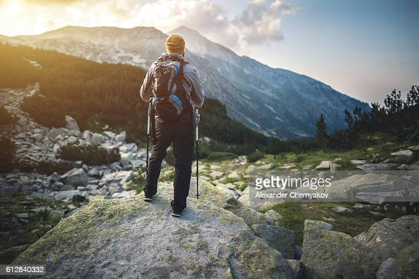 Traveler with backpack looks on a mountain peak on sunset