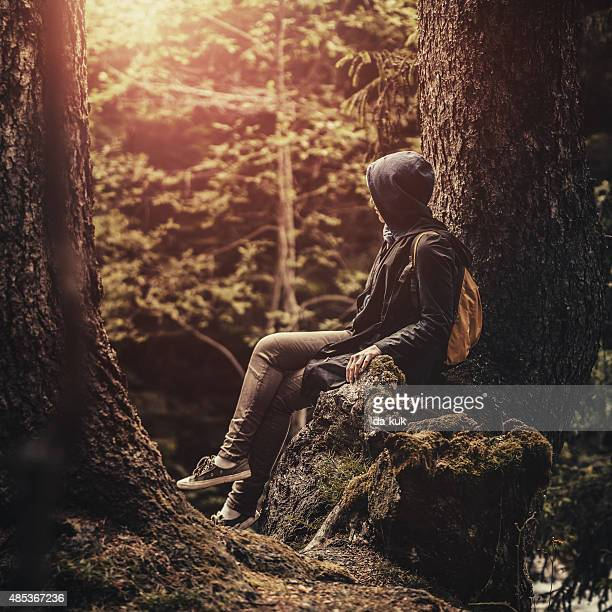 Traveler with backpack sitting in the forest at sunset