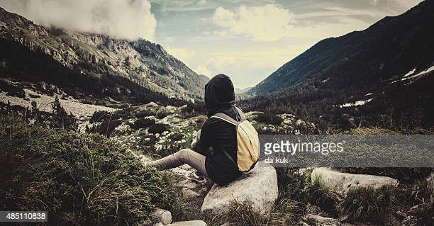 Traveler with backpack sitting in the mountains