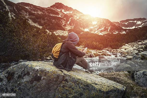 Los viajeros con mochila sentado en una big stone con teléfono inteligente