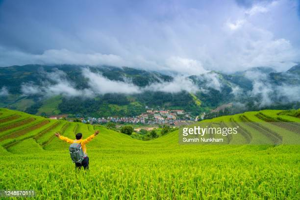 traveler with backpack taking photo on countryside among terrace rice fields with cityscape countryside background. on vacation of harvest season at mu cang chai, yenbai, northern vietnam. - terrassenfeld stock-fotos und bilder