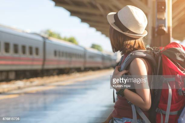 traveler with backpack waiting for a train at train station. travel and vacation concept - rucksacktourist stock-fotos und bilder