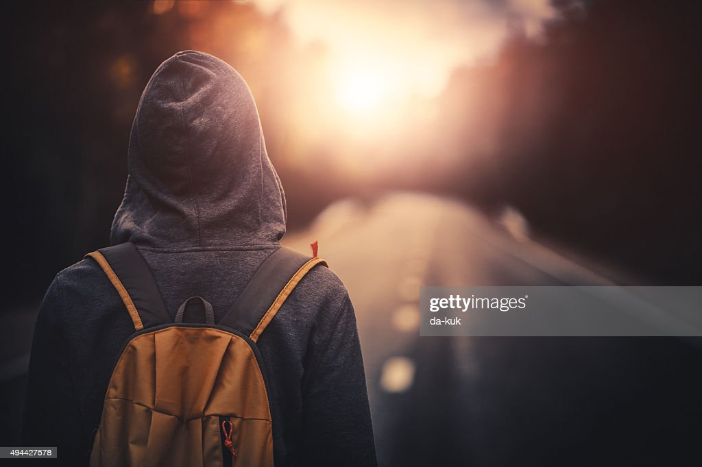 Traveler with backpack walking forward alone at sunset : Stock Photo