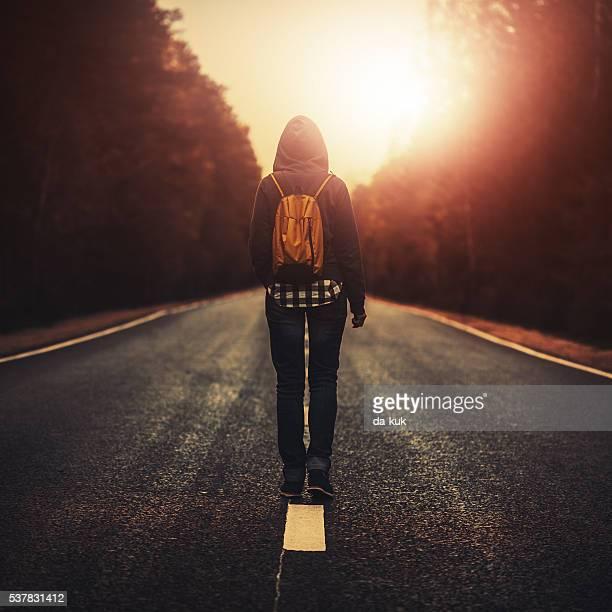 Reisende mit Rucksack zu Fuß nach vorn, allein bei Sonnenuntergang