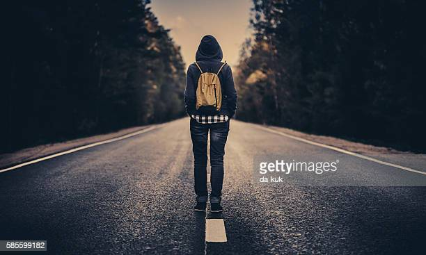 Traveler with backpack walking forward alone