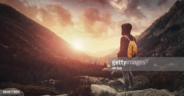 Reisende mit Rucksack zu Fuß in die Berge bei Sonnenuntergang