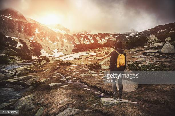 Traveler with backpack walking in mountains at sunset