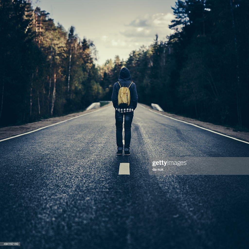 Reisende mit Rucksack zu Fuß auf der Straße : Stock-Foto