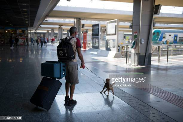 A traveler with his dog walks with luggage to the interregional train at the Porta Nuova railway station on June 03 2020 in Turin Italy Today 3 June...