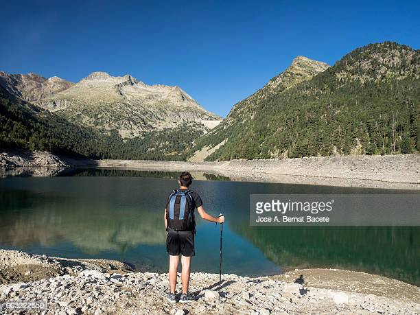 Traveler with his rucksack and stick opposite to a lake surrounded with mountains , Pyrenees, France