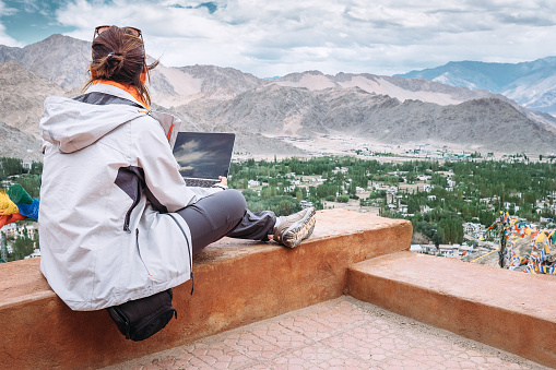 Traveler with laptop sits on top view point on the mountain valley 648868332