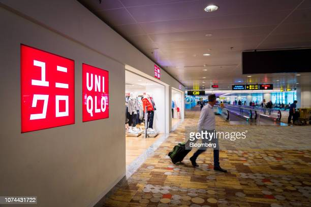 A traveler with luggage exits a a Uniqlo store operated by Fast Retailing Co at Terminal 1 of Changi Airport in Singapore on Thursday Dec 13 2018...
