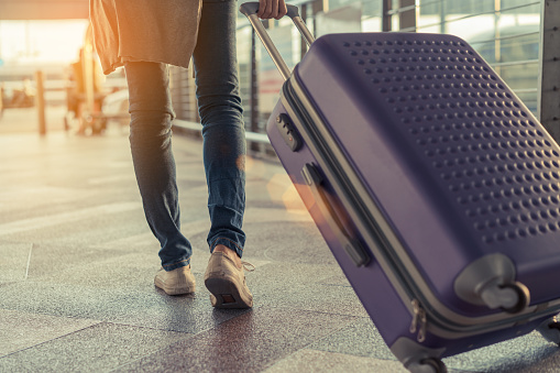 Traveler with suitcase in airport concept.Young girl  walking with carrying luggage and passenger for tour travel booking ticket flight at international vacation time in holiday rest and relaxation. 874914576