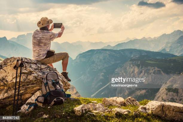 traveler with tablet in the mountains - dolomiti foto e immagini stock
