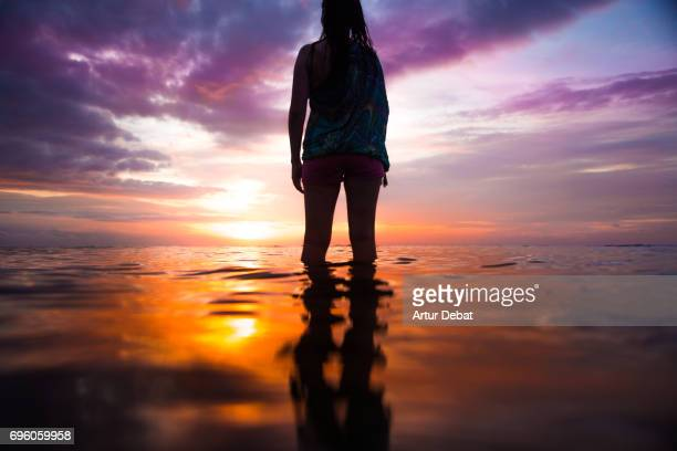 Traveler woman contemplating sunset from water in the beach with beautiful colors during travel vacations in Indonesia.