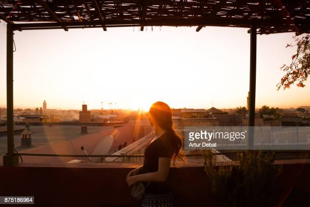 Traveler woman contemplating the Marrakech cityscape during sunset taken from building terrace with mosque silhouettes and nice colors in the sky during travel vacations in Morocco.