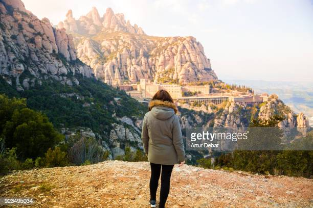 Traveler woman contemplating the monastery of Montserrat between the stunning rock formations mountain in Catalonia.