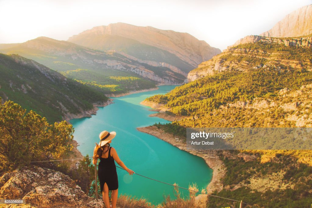 Traveler woman contemplating the stunning view from viewpoint on top of the edge with cliff and stunning views of the lake and mountains in the Catalan Pyrenees mountains. : Stock Photo