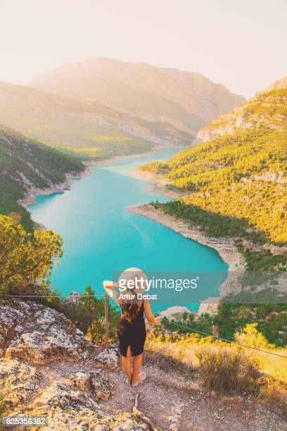 Traveler woman contemplating the stunning view from viewpoint on top of the edge with cliff and stunning views of the lake and mountains in the Catalan Pyrenees mountains.
