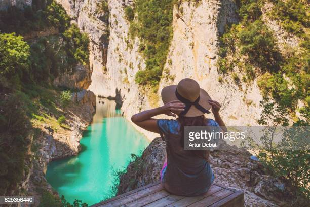 Traveler woman contemplating the stunning view from viewpoint on top of the edge with cliff and stunning views of the river in the Congost de Montrebei with mountains in the Catalan Pyrenees.