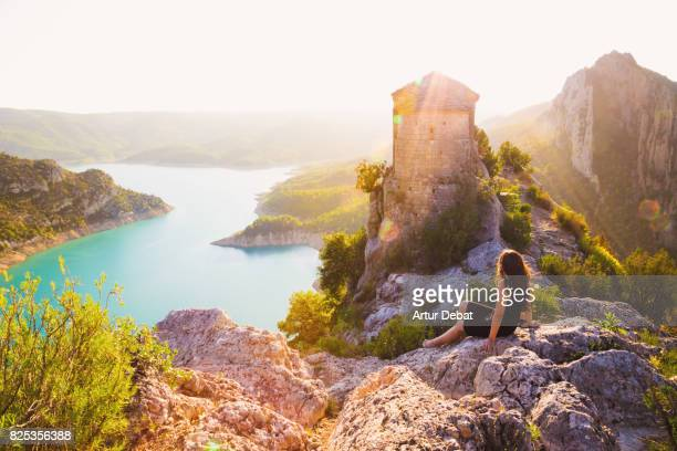 Traveler woman contemplating the stunning view of a ancient chapel on top of the edge with cliff and stunning views of the lake and mountains in the Catalan Pyrenees mountains.