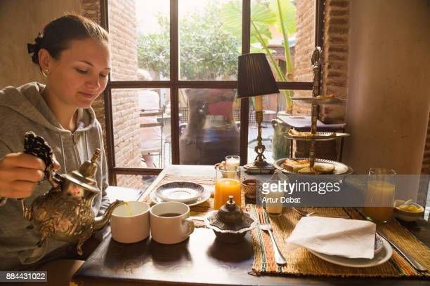 Traveler woman enjoying breakfast in riad hotel in the Marrakech medina district, taking mint tea with traditional moroccan food in the morning during travel vacations in Morocco.