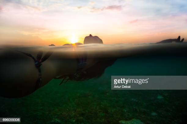 Traveler woman floating on water resting during sunset moment after long day during travel vacations in the paradise islands of Indonesia with stunning colors in the sky and reflections on water.