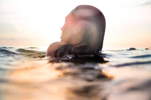 Traveler woman floating on water resting during sunset moment after long day during travel vacations in the paradise islands of Indonesia with stunning colors in the sky and reflections on water. - gettyimageskorea