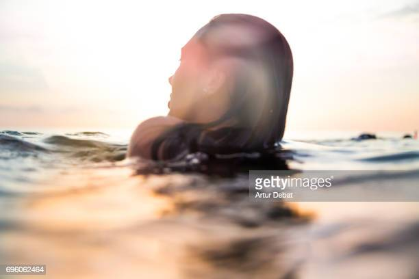 traveler woman floating on water resting during sunset moment after long day during travel vacations in the paradise islands of indonesia with stunning colors in the sky and reflections on water. - auf dem wasser treiben stock-fotos und bilder