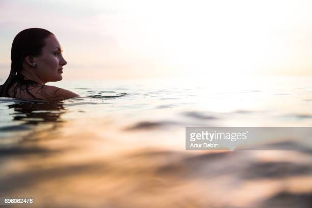 traveler woman floating on water resting during sunset moment after long day during travel vacations in the paradise islands of indonesia with stunning colors in the sky and reflections on water. - gili trawangan stock photos and pictures