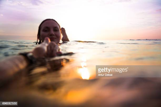 Traveler woman floating on water resting during sunset moment after long day during travel vacations in the paradise islands of Indonesia with stunning colors in the sky and reflections on water holding hand to couple.