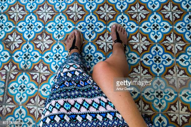 Traveler woman from personal perspective taking picture of her legs with colorful dress and the background the tiles of the floor in a old house of the Marrakech medina.