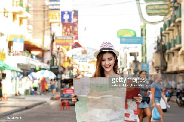traveler woman looking map planning and find location for travel trip, tourism alone with bag backpack on street at city. travel and vacation concept. - cape canaveral stock pictures, royalty-free photos & images