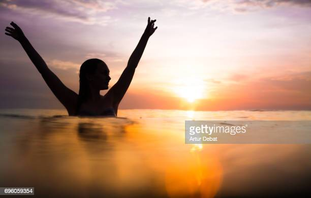 Traveler woman swimming on water contemplating the sunset moment after long day during travel vacations in the paradise islands of Indonesia with stunning colors in the sky and reflections on water.