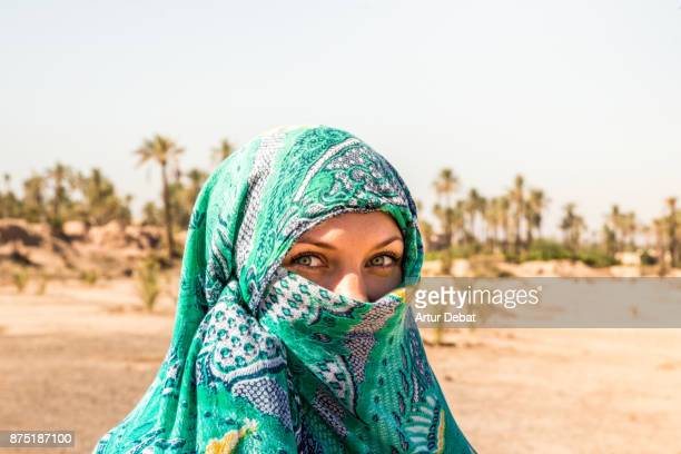 Traveler woman wearing a green scarf covering the face like berber that match with her green eyes in the Palmeraie of Marrakesh, a nice palm tree place with desert and dry landscape, during road trip in the Morocco.