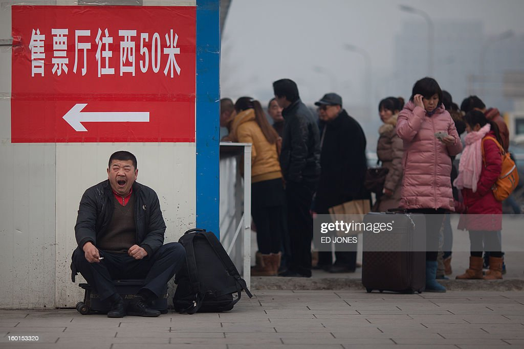 A traveler yawns as he sits with his luggage next to a ticket queue at Beijing Railway Station in Beijing on January 27, 2013. The world's largest annual migration began in China with tens of thousands in the capital boarding trains to journey home for next month's Lunar New Year celebrations. AFP PHOTO / Ed Jones