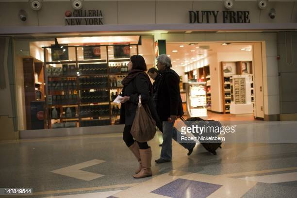 Travelers and tourists walk past shops in a corridor March 25 2012 at the John F Kennedy International Airport in Queens New York JFK International...