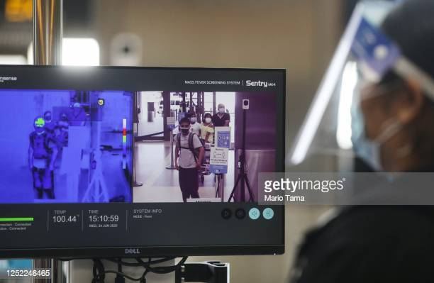 Travelers are displayed on a video screen walking past a test system of thermal imaging cameras which check body temperatures at Los Angeles...