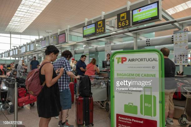 Travelers are partially screened by a cabin luggage related sign while waiting at TAP Air Portugal checkin counters in Terminal 1 of Barcelona El...