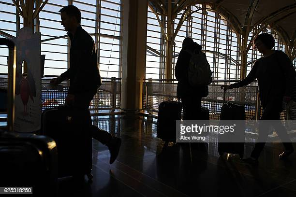 Travelers are seen at Ronald Reagan Washington National Airport November 23 2016 in Arlington Virginia AAA has predicted that it will be more crowded...