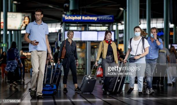 Travelers are seen at Schiphol airport, on July 19, 2020 near Amsterdam. - After coronavirus lockdowns that brought civil aviation to nearly a...