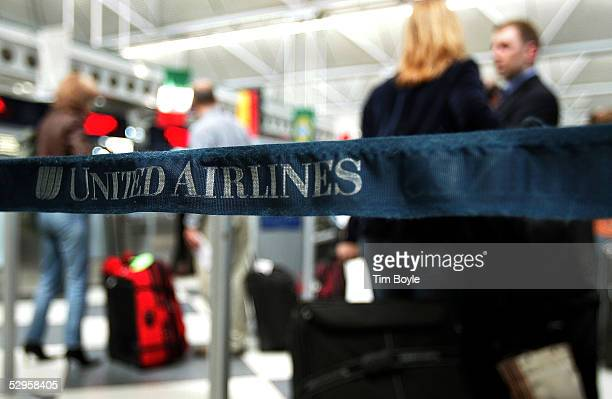 Travelers are seen beyond stanchion strapping in the United Airlines terminal at O'Hare International Airport May 20 2005 in Chicago Illinois Members...