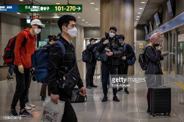 Travelers are seen wearing facemasks as protection from COVID-19 inside Incheon International Airport on March 10, 2020 in Incheon, South Korea....