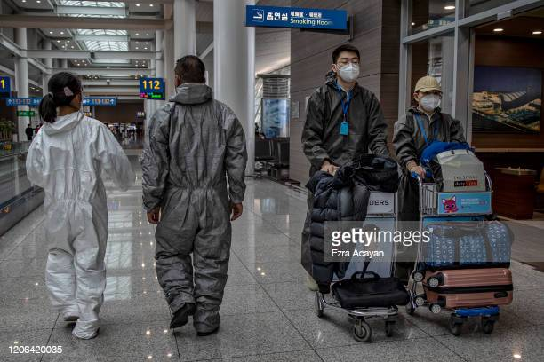 Travelers are seen wearing rain suits and facemasks to protect themselves from COVID-19 while waiting for their flight inside Incheon International...