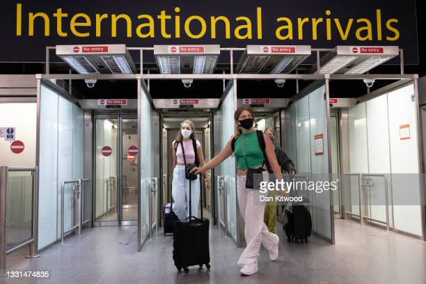 Travelers arrive at Gatwick Airport on July 30, 2021 in London, England. Restrictions to and from the UK remain in place as Coronavirus continues to...