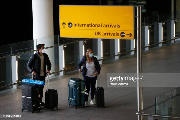 "Travelers arrive at Heathrow Airport on January 17, 2021 in London, England. Tomorrow morning the UK will close its so-called ""travel corridors"" with..."
