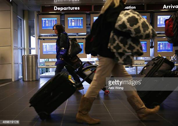 Travelers arrive at Ronald Reagan Washington National Airport November 26 the day before Thanksgiving outside Washington DC in Arlington VirginiaThe...