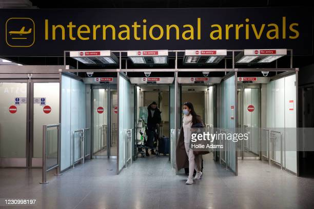 Travelers arrive at the North Terminal at Gatwick Airport on February 6, 2021 in London, England. The UK government has confirmed that anyone...
